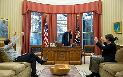 Advisers Ben Rhodes, left, and Tony Blinken cheer as Barack Obama talks on the phone with John Kerry about nuclear negotiations with Iran, on November 23, 2013. (photo credit: Pete Souza/White House)