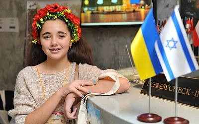 A Jewish girl wearing a traditional Ukrainian wreath, or 'vinok,' stands in the lobby of Lviv's Dnister Hotel, where Israeli and Ukrainian flags stand side-by-side during the Limmud FSU conference in Lviv, Ukraine, November 6-10, 2014. (photo credit: Yossi Aloni)