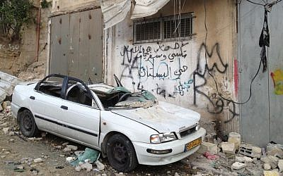 A car stands destroyed beneath the bombed out home of Palestinian terrorist Abdul Rahman Al-Shaloudi in Silwan, November 19, 2014 [photo credit: Elhanan Miller/Times of Israel]