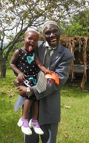 JJ Keki, with granddaughter Ranita, serves as a Luganda translator, and reads the Haftorah in Luganda every week. (Melanie Lidman/Times of Israel)