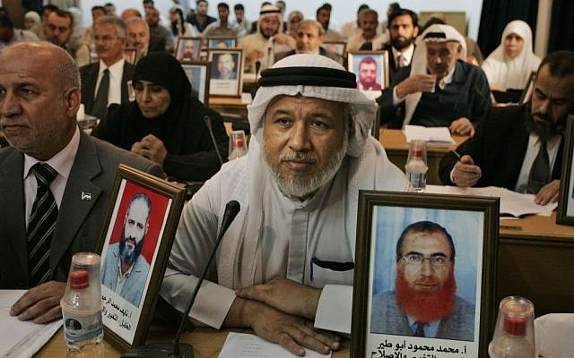 Hamas lawmakers in the Gaza Strip display pictures of deputies detained by Israel during a Palestinian Legislative Council meeting in Gaza City, November 7, 2007 (photo credit: AP/Hatem Moussa)