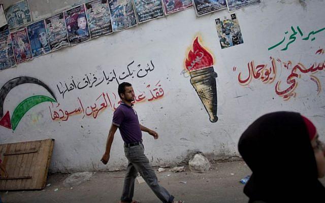 Palestinians walk through an alley of the West Bank refugee camp of Balata, near Nablus (Photo credit: Bernat Armangue/AP)