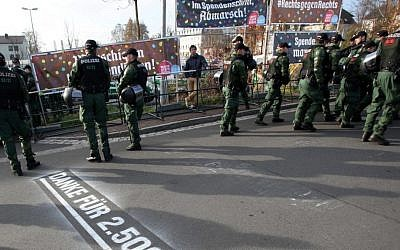 Police stand in front of banners reading 'Donate with every step, march' (top left), and '#Right against right' (top right), during a far-right march in Wunsiedel, southern Germany. Letters on the ground say 'Thanks for euro 2,500!' November 15, 2014. (photo credit: AP/dpa, Fricke)