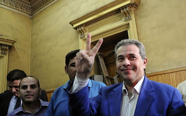 Tawfiq Okasha flashes the victory sign in an Egyptian court, where he was accused of inciting the death of former Islamist president Mohammed Morsi, September 1, 2012 (photo credit: AP/Mohammed Assad)