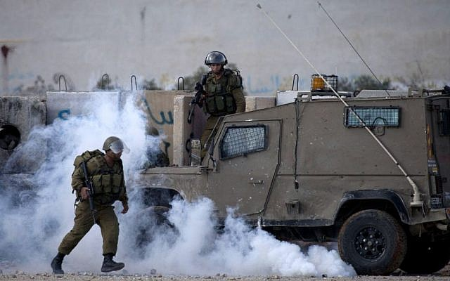 Israeli soldiers clash with Palestinian protesters near the West Bank city of Ramallah, November 18, 2014 (Photo credit: Majdi Mohammed/AP)