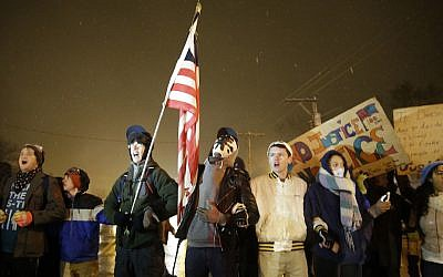 Protesters stand in front of the Ferguson Police Department, Wednesday, Nov. 26, 2014, in Ferguson, Mo. (AP Photo/David Goldman)