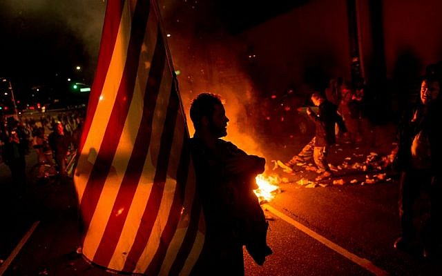 James Cartmill holds an American flag while protesting in Oakland, Caliornia, on Monday, Nov. 24, 2014, after the announcement that a grand jury decided not to indict Ferguson police officer Darren Wilson in the fatal shooting of Michael Brown. (photo credit: AP Photo/Noah Berger)