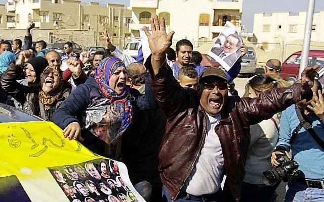Supporters of former Egyptian President Hosni Mubarak celebrate after hearing the verdict of his trial outside a police academy on the outskirts of Cairo, Saturday, Nov. 29, 2014. The court on Saturday dismissed murder charges against Mubarak in connection with the killing of protesters in the 2011 uprising that ended his nearly three-decade reign. (photo credit: AP/Ahmed Abd El-Latif, El Shorouk Newspaper)