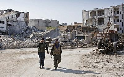 Kurdish People's Protection Units (YPG) soldiers walk near the town entrance circle heading to their strongholds in Kobani, Syria, earlier this year. (photo credit: AP/Jake Simkin)