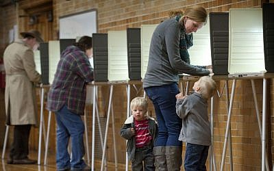 Debbie Baldwin fills out her ballot on Election Day with the company of her sons Joshua, 4, and Luke, 2, at Aberdeen School in Grand Rapids, Mich., Tuesday, Nov. 4, 2014. (photo credit: AP/The Grand Rapids Press, Chris Clark)