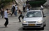 Protesters throwing stones at a car in the Silwan neighborhood of Jerusalem in 2011. (Yonatan Sindel / Flash90)