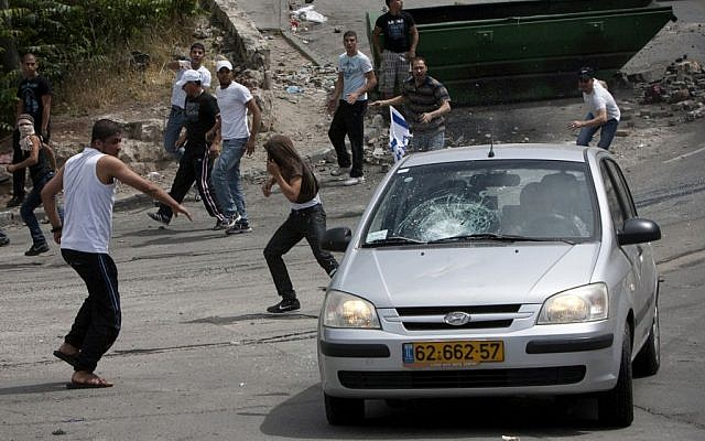 Protesters throwing stones at a car in the Silwan neighborhood of Jerusalem in 2011. (Yonatan Sindel / Flash90)