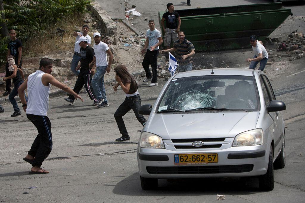 Protesters throwing stones at a car in the Silwan neighborhood of Jerusalem in 2011. (Photo credit: Yonatan sindel / Flash90)