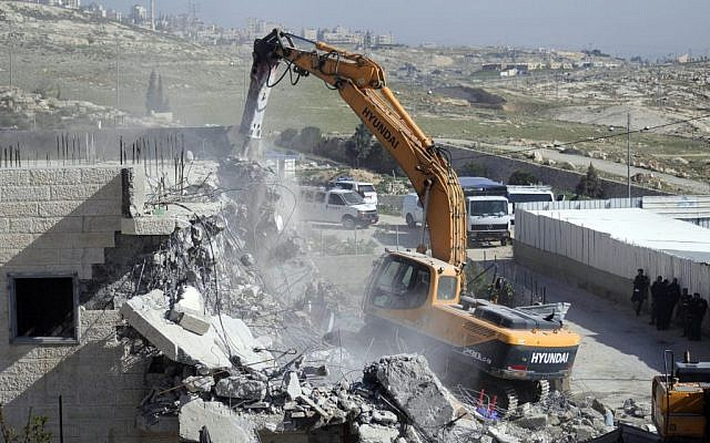 File: Bulldozers of the Jerusalem municipality destroy a Palestinian house in the East Jerusalem neighborhood of Al-Tur on March 26, 2014, on the grounds that it was built without a construction permit. (photo credit: Sliman Khader/Flash90/File)