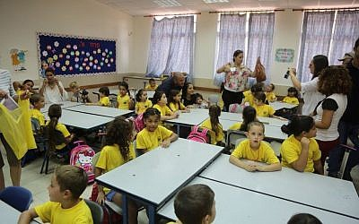 Itamar Shimoni welcoming kids to an Ashkelon school on September 1, 2014. (photo credit: Edi Israel/Flash90)