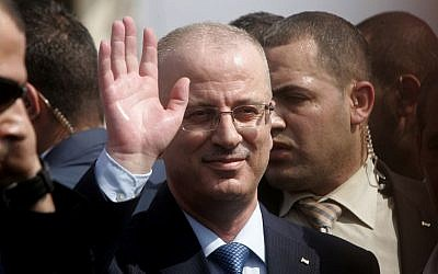 Palestinian Authority Prime Minister Rami Hamdallah waves to citizens during his visit to Beit Hanoun in the northern Gaza Strip, October 9, 2014. (photo credit: Abed Rahim Khatib/Flash90)