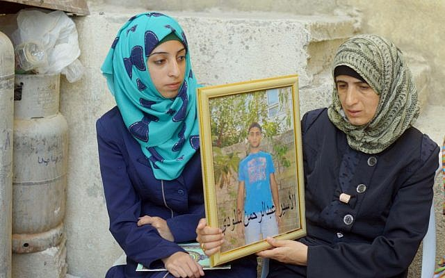Female family members of Jerusalem terrorist Abdul Rahman Shaloudi hold up a portrait of him in Silwan, October 23, 2014 (photo credit: Sliman Khader/Flash90)