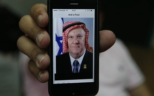 An iPhone logged into Facebook shows a user's post of a manipulated picture of President, Reuven Rivlin, with a keffiyeh. October 30, 2014. (Photo credit: Nati Shohat/Flash90)