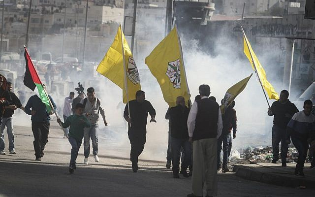 Clashes between Israeli forces and Palestinian protesters carrying Fatah flags following a rally on November 2, 2014 at the Qalandia checkpoint north of Jerusalem (photo credit: Issam Rimawi/Flash90)