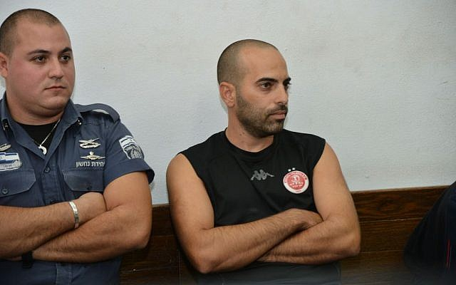 The soccer fan who burst into the field during the Hapoel Tel Aviv and Maccabi Tel Aviv game November 3 and attacked a player is brought to the Tel Aviv District Court on November 4, 2014. (photo credit: Flash90)
