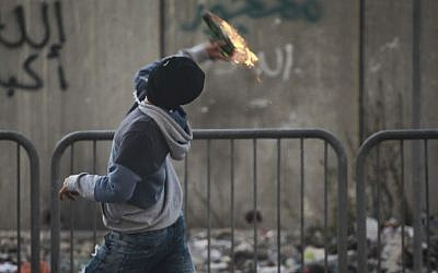 Illustrative photo of a Palestinian throwing a Molotov cocktail at Israeli forces at the entrance to the Shuafat refugee camp on November 05, 2014. (Hadas Parush/FLASH90)