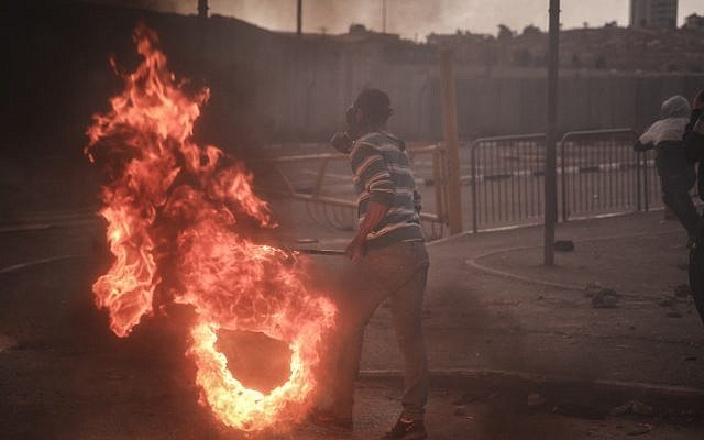 ILLUSTRATIVE: Palestinian youths clash with Israeli Border Police at the entrance to the Shuafat refugee camp on November 5, following a terrorist attack that day in Jerusalem by a resident of the camp. (Hadas Parush/FLASH90)