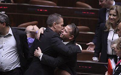 New Israeli Interior Minister Gilad Erdan hugging MK Eitan Kabel at the Israeli parliament during a plenum session on November 5, 2014. (Photo credit: Issac Harari/Flash90)