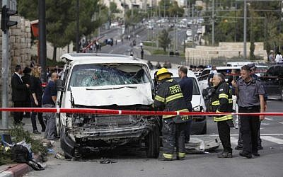 Israeli security personnel at the site where an Arab man from the East Jerusalem neighborhood of Shuafat drove his car into a crowd of people waiting at a Jerusalem Light Rail station, November 5, 2014. (photo credit: Yonatan Sindel/Flash90)
