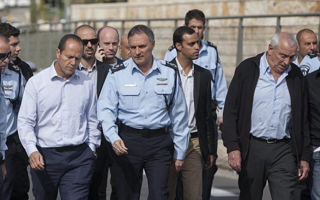 Mayor Nir Barkat, left, and Israel Police chief Yohanan Danino, center, at the site where an Arab man from the East Jerusalem neighborhood of Shuafat drove his car into a crowd of people waiting at a light rail station in Jerusalem, November 5, 2014. (photo credit: Yonatan Sindel/FLASH90)
