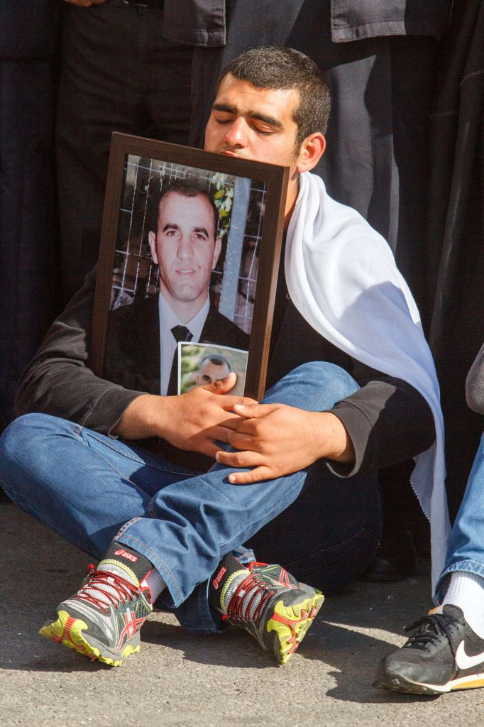 A mourner holds a photograph of Border Police officer Jedan Assad, at his funeral in the northern Druze village of Beit Jann, on November 6, 2014. Asad was killed by a Hamas terrorist who rammed his minivan into a crowd in Jerusalem on November 5. (Photo credit: FLASH90)