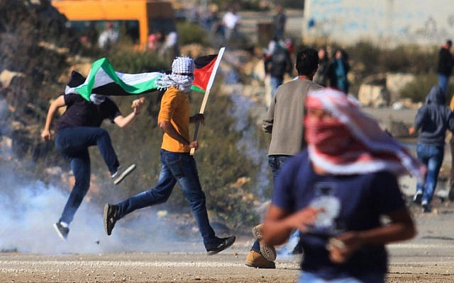 Masked Palestinian youths clash with Israeli security forces near the West Bank city of Ramallah on November 6, 2014. (photo credit: STR/Flash90)