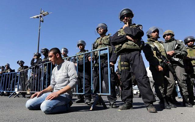 Palestinians pray as Israeli policemen watch over during Friday prayers in the East Jerusalem neighborhood of Ras El Amud November 7, 2014. (Photo credit: Sliman Khader/Flash90)