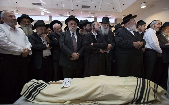 Mourners standing next to the body of Shalom Aharon Ba'adani during his funeral in Jerusalem on November 7, 2014. Ba'adani died Friday after being injured when a terrorist rammed his minivan into a crowd waiting for a train in Jerusalem on November 5. (Photo credit: Yonatan Sindel/Flash90)
