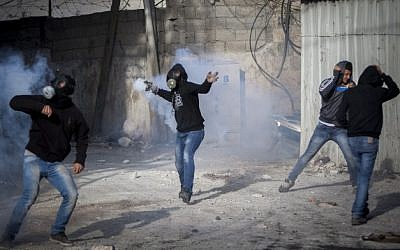 Palestinian youths throw stones during clashes with Israeli Border Police in the Shuafat Refugee Camp, in Jerusalem, following Friday prayers on November 7, 2014. (Photo credit: Yonatan Sindel/Flash90)
