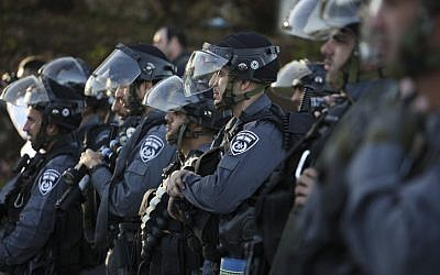 Israeli police officers wait for command to advance towards rioters throwing rocks during clashes at the entrance to the Arab village of Kfar Kanna, in northern Israel, on November 8, 2014. (photo credit: Hadas Parush/Flash90)