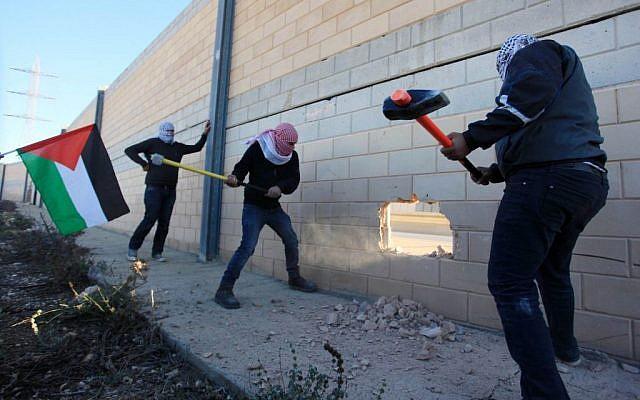 Palestinians seen smashing a section of the West Bank security barrier at Bir Nabala, between Jerusalem and Ramallah, on November 8, 2014. (Photo credit: STR/Flash90)