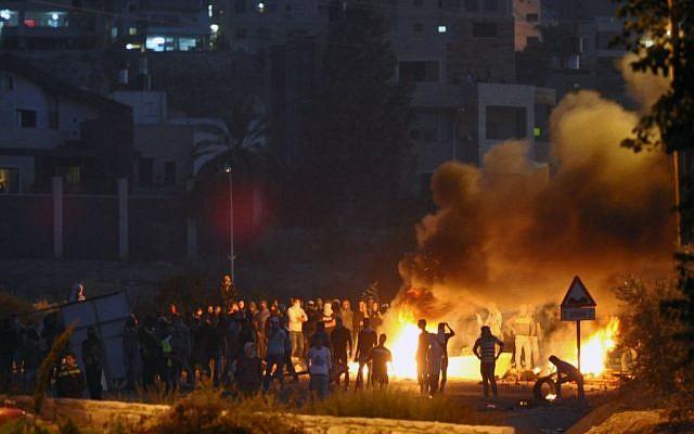 Palestinian youth seen throwing rocks towards Israeli Border Policemen at the entrance to the Arab village, Kfar Kanna, in Northern Israel, on November 9, 2014. (photo credit: Flash90)
