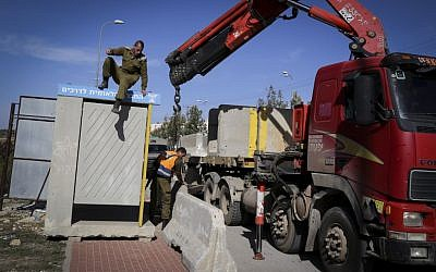 Israeli soldiers seen placing large cement blocks at a bus stop near the Jewish settlement of Alon Shvut on November 11, 2014. (Photo credit: Gershon Elinson/Flash90)