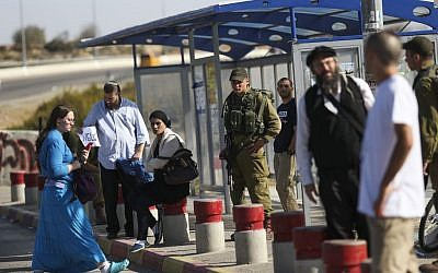 Israelis stand near soldiers on November 11, 2014, at a bus stop at the entrance to the West Bank settlement of Alon Shvut where a Palestinian terrorist killed Dalia Lemkus the day before. (Photo credit: Nati Shohat/Flash90)