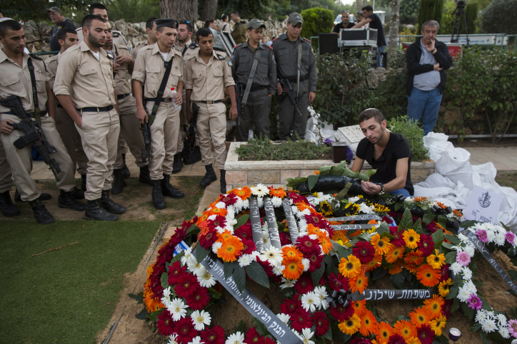 Twin brother of Israeli soldier Almog Shiloni stands by his grave at the military cemetery on Mount Herzl in Jerusalem on November 11, 2014. (photo credit: Yonatan Sindel/Flash90)