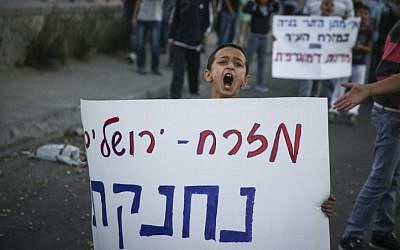 Palestinian boy marches with a sign reading 'East Jerusalem is choking,' during a demonstration in Issawiya, East Jerusalem, on November 12, 2014. (photo credit: Hadas Parush/Flash90)