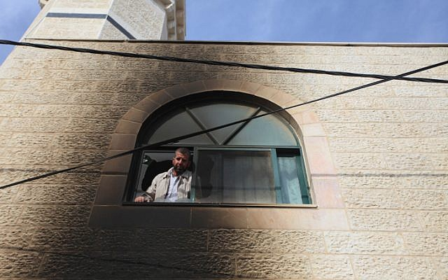 Palestinians inspect the mosque that was allegedly set on fire by Israeli settlers in al-Mughayir, in the West Bank on November 12, 2014. (photo credit: STR/Flash90)