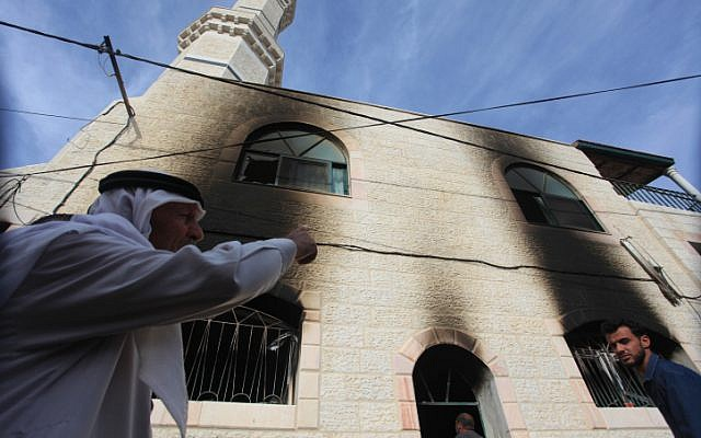 Palestinians inspect a mosque that was torched in the village of al-Mughayir, in the West Bank near the Jewish settlement of Shilo, on November 12, 2014. (photo credit: STR/Flash90)