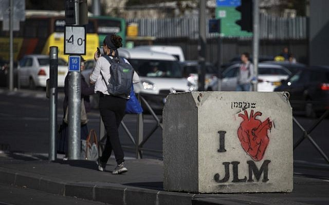 People pass by a graffiti painted concrete block that was placed following the recent hit-and-run terror attacks. (Photo credit: Hadas Parush/Flash90)