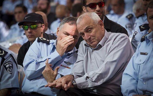 Police chief Yohanan Danino, left, whispering in the ear of Public Security Minister Yitzhak Aharonovitch on Thursday November 13, 2014. (photo credit: Miriam Alster/Flash90)