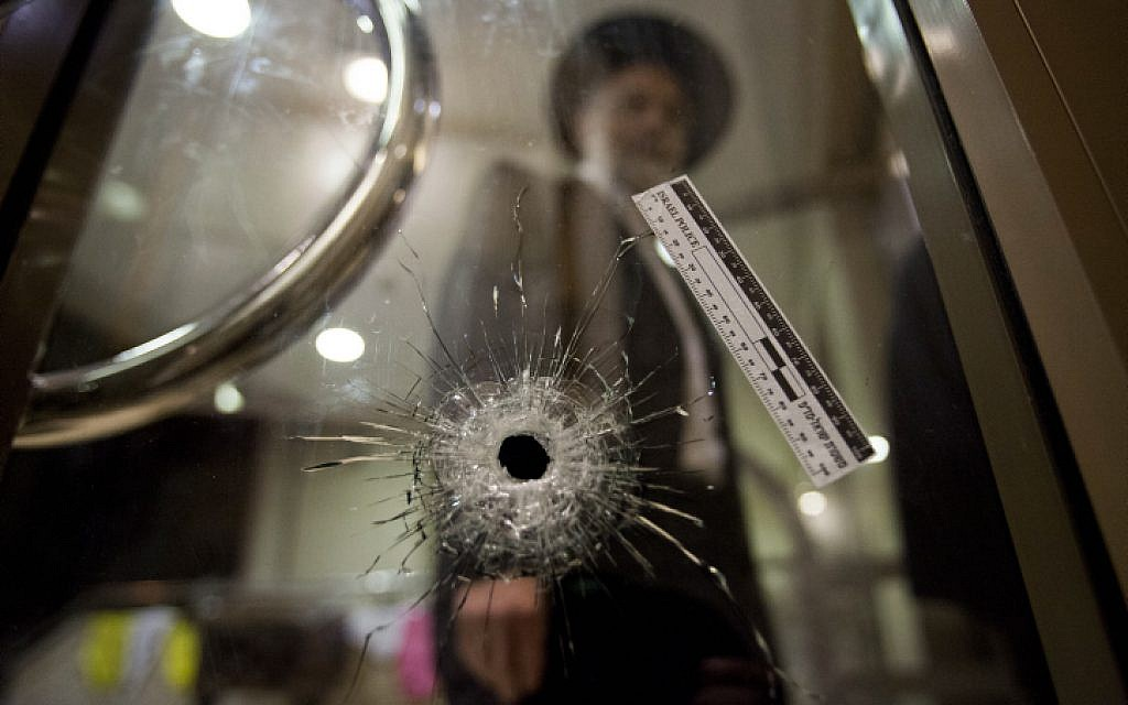 A congregant at the Har Nof synagogue where five people were killed by Palestinian terrorists examines a bullet hole. November 18, 2014. (photo credit: Noam Revkin Fenton/Flash90)