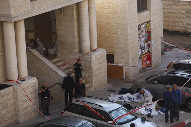 Israeli police outside the Kehilat Yaakov synagogue in Jerusalem after a terror attack there on November 18, 2014. The bodies of two terrorists covered with plastic are seen on the ground. (photo credit:  Yonatan Sindler/FLASH90)