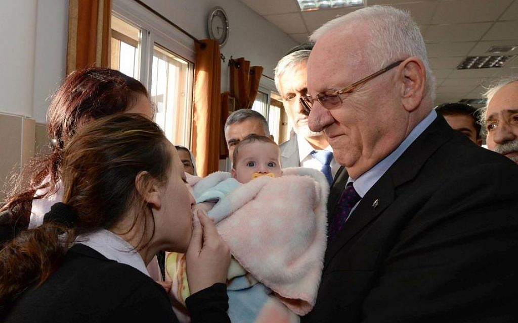 Reuven Rivlin holds the baby daughter of slain police officer Zidan Saif while attending his funeral in the Druze village of Yenuh-Jat on November 19, 2014. Photo credit: Mark Neyman/GPO)
