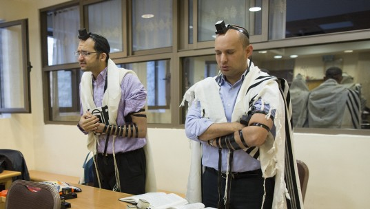 Economy Minister Naftali Bennet (R) prays inside a synagogue where two terrorists from East Jerusalem killed five people on Tuesday. November 19, 2014. (photo credit: Yonatan Sindel/Flash90)