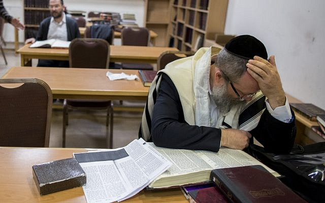 An ultra-Orthodox man peers over a Talmud in the Jerusalem synagogue where five people were killed a day earlier. November 19, 2014. (photo credit: Yonatan Sindel/Flash90)